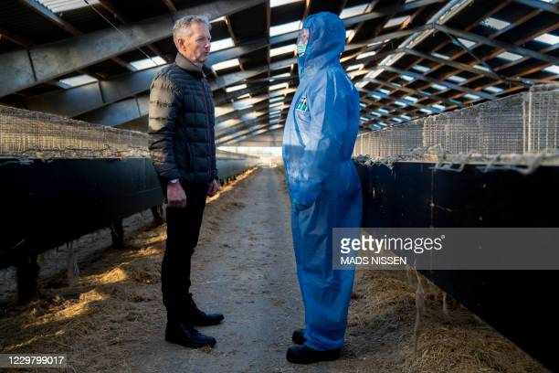 Denmark's Prime Minister Mette Frederiksen and mink breeder Peter Hindbo talk as they visit the closed and empty farm near Kolding, Denmark, on...