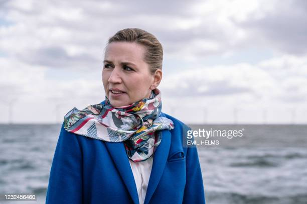 Denmark's Prime Minister Mette Frederiksen is seen as she stands on a boat with the wind turbines of the Middelgrunden offshore wind farm in the...