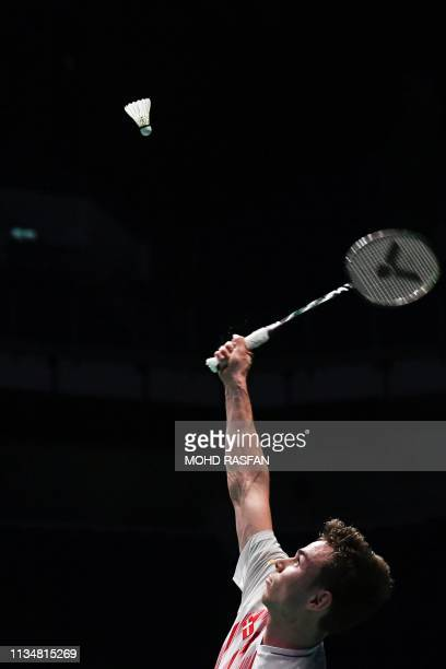 Denmark's Rasmus Gemke hits a return against Japan's Kenta Nishimoto during their men's singles match at the Malaysia Open badminton tournament in...