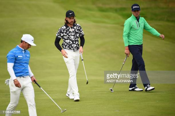 Denmark's Thorbjorn Olesen, England's Tommy Fleetwood and US golfer Justin Thomas walk on the 2nd green during the second round of the British Open...