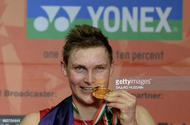 Denmark's Viktor Axelsen poses for pictures with his gold medal after winning the men's singles final badminton match against Chou Tien Chen of...