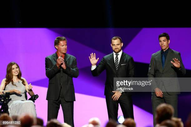 Denna Laing former NHL player Bobby Carpenter Nick Foligno of the Columbus Blue Jackets and Travis Hamonic of the New York Islanders stand onstage...
