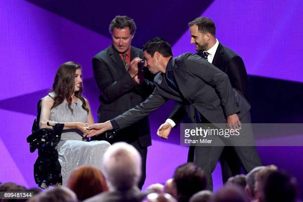R Denna Laing former NHL player Bobby Carpenter Nick Foligno of the Columbus Blue Jackets and Travis Hamonic of the New York Islanders stand onstage...