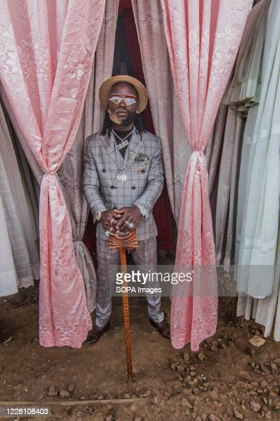 Dennis Anzere, a young fashionista takes a pose in his vintage suit. Young people in Kibera slums wear carefully selected, fitting,...