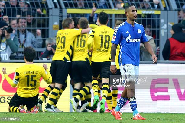Dennis Aogo of Schalke looks dejected whilst players of Dortmund celebrate the first team goal during the Bundesliga match between Borussia Dortmund...