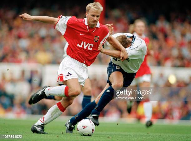 Dennis Bergkamp of Arsenal holds off John Scales of Tottenham Hotspur during an FA Carling Premiership match at Highbury on August 30 1997 in London...