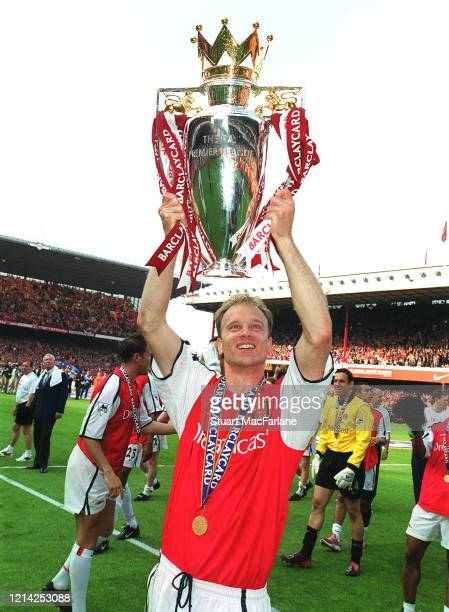 Dennis Bergkamp of Arsenal with the Premier League Trophy after the Premier League match between Arsenal and Everton on May 11 2002 in London England