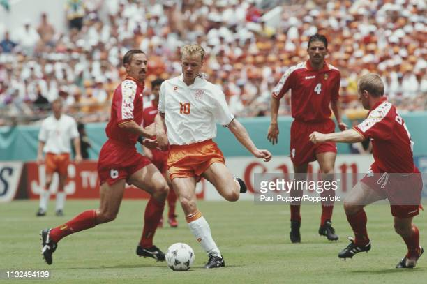 Dennis Bergkamp of Netherlands pictured with the ball as Belgian players Marc Degryse and Michel de Wolf move in during play between Belgium and...