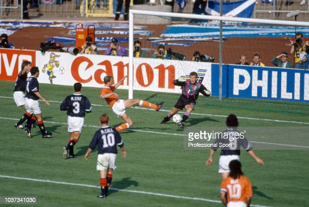 Dennis Bergkamp of the Netherlands scores past Scotland goalkeeper Andy Goram during the UEFA Euro 92 Group 2 match between the Netherlands and...