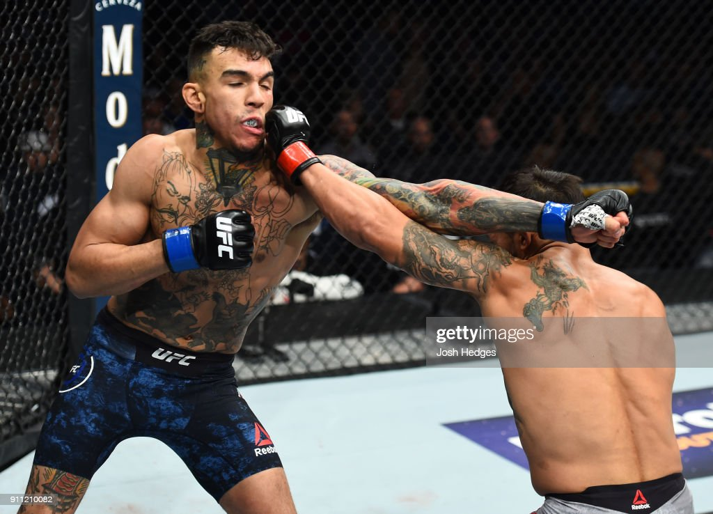 Dennis Bermudez punches Andre Fili in their featherweight bout during a UFC Fight Night event at Spectrum Center on January 27, 2018 in Charlotte, North Carolina.