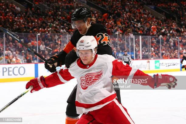 Dennis Cholowski of the Detroit Red Wings battles Oskar Lindblom of the Philadelphia Flyers in the second period at the Wells Fargo Center on...