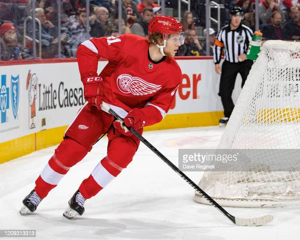 Dennis Cholowski of the Detroit Red Wings skates around the net with the puck against the Minnesota Wild during an NHL game at Little Caesars Arena...