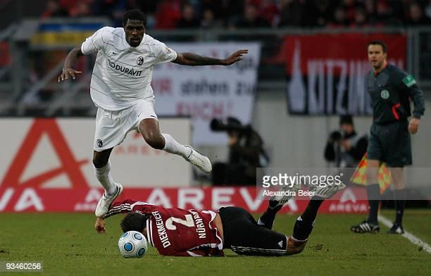Dennis Diekmeier of Nuernberg falls as Mohamadou Idrissou of Freiburg runs for the ball during the Bundesliga match between 1. FC Nuernberg and SC...