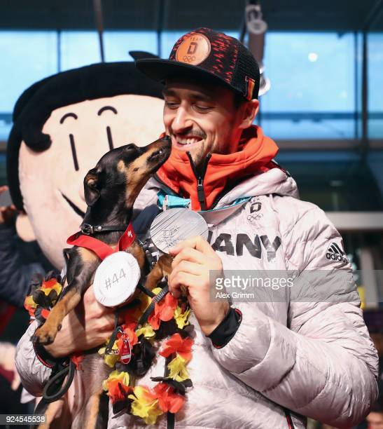 Dennis Endras of the German ice hockey team is welcomed by his dog Tia during the welcome ceremony for the members of Team Germany after their return...