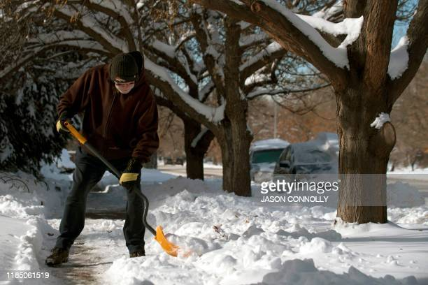 Dennis Faaborg of Denver Colorado shovels a sidewalk on November 27 2019 A pair of storms packing heavy snow and hurricaneforce winds left tens of...