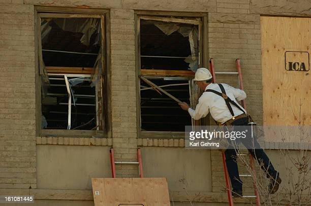 Dennis Flesher prepared to board up a broken secondstory window in a vacant building at 15th and Little Raven Saturday afternoon where firefighters...