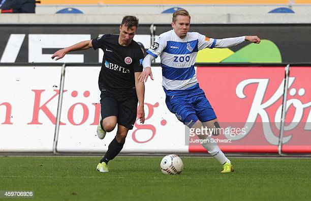 Dennis Grote of Duisburg tackles Tobias Jaenicke of WehenWiesbaden during the Third League match between MSV Duisburg and SV Wehen Wiesbaden at...