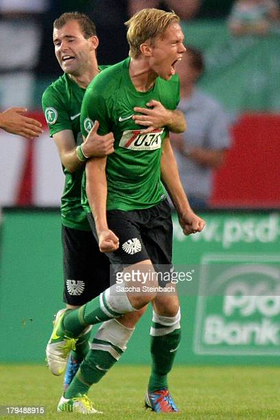 Dennis Grote of Muenster celebrates after scoring his team's first goal with Amaury Bischoff during the 3 Liga match between Preussen Muenster and...