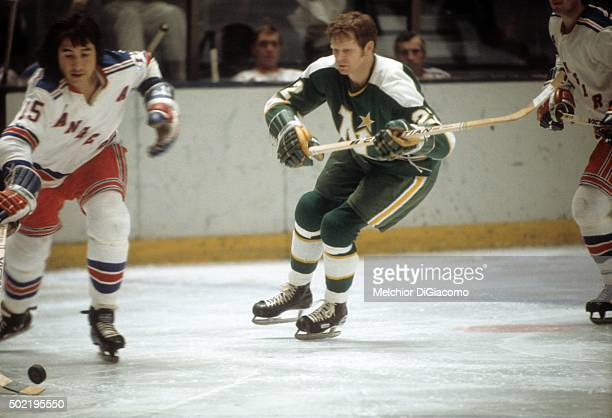Dennis Hextall of the Minnesota North Stars goes to defend as Jim Neilson of the New York Ranges skates with the puck during an NHL game circa 1972...