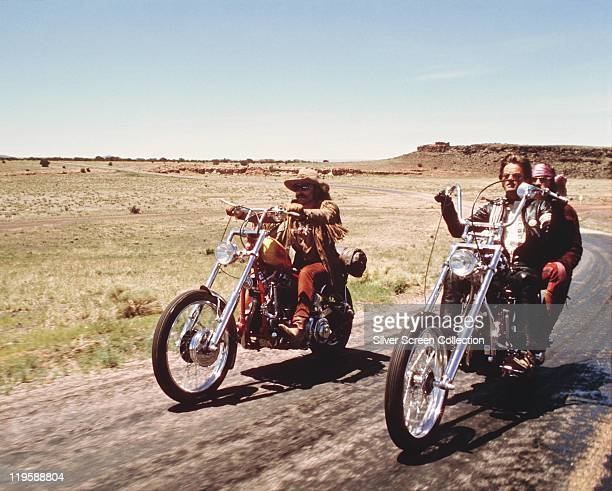 Dennis Hopper and Peter Fonda riding their chopper motorcycles with Luke Askew on the back of his motorcyle in a publicity still issued for the film...