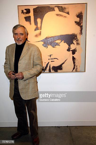 Dennis Hopper poses with the Andy Warhol portrait of him at Art Basel Miami where his art work is displayed in Miami Beach Florida