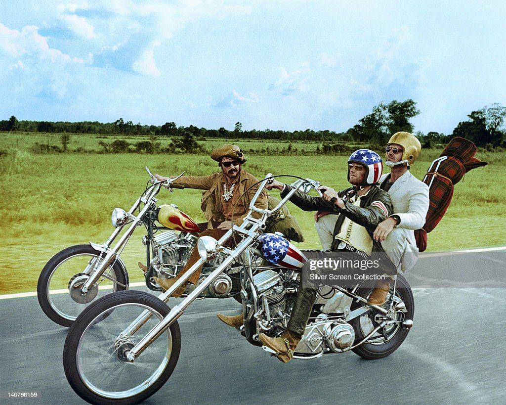 Dennis Hopper (1936-2010), US actor, and Peter Fonda, wearing a stars-and-stripes helmet, riding their chopper motorcycles, with Jack Nicholson, US actor, wearing a gold American football helmet, on the back of Fonda's motorcycle, in a publicity still issued for the film, 'Easy Rider', USA, 1969. The film, directed by Dennis Hopper, starred Hopper as 'Billy', Fonda as 'Wyatt', and Nicholson as 'George Hanson'.
