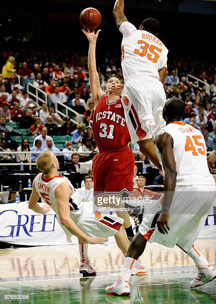 Dennis Horner of the NC State Wolfpack puts up a shot between Tanner Smith and Trevor Booker of the Clemson Tigers in their first round game in the...