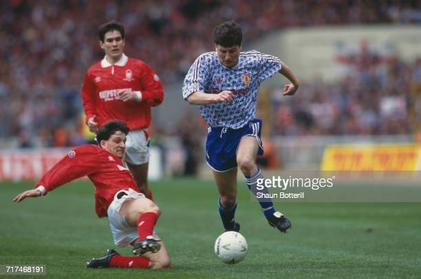 Dennis Irwin of Manchester Utd holds onto the ball from the Nottingham Forest defender Gary Crosby as Nigel Clough looks on during their Rumbelows...