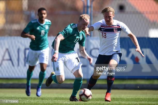 Dennis Jastrzembski of Germany is challenged by Sebastian Jarl of Norway during the UEFA Elite Round match between Norway U19 and Germany U19 at...
