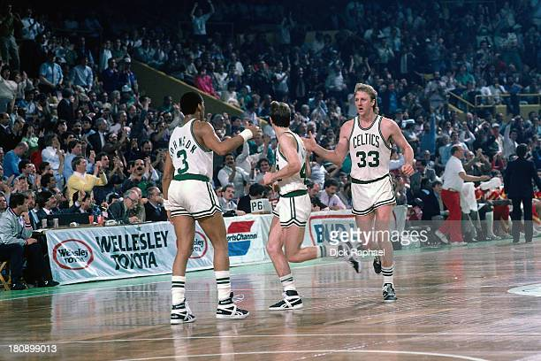 Dennis Johnson Danny Ainge and Larry Bird of the Boston Celtics exchange high fives as they run back downcourt during a game circa 1986 at the Boston...