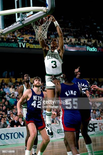 Dennis Johnson of the Boston Celtics dunks against Albert King and Mike Gminsky of the New Jersey Nets during an NBA game played in 1986 at the...
