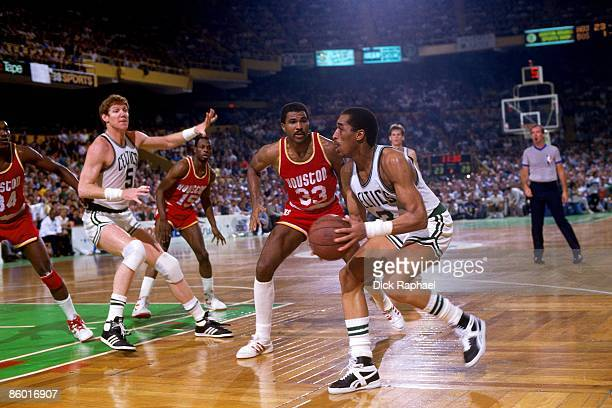 Dennis Johnson of the Boston Celtics looks to pass against Robert Reid of the Houston Rockets during an NBA game played in 1986 at the Boston Garden...