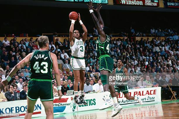 Dennis Johnson of the Boston Celtics shoots against Ben Coleman of the Milwaukee Bucks during a game played circa 1989 at the Boston Garden in Boston...
