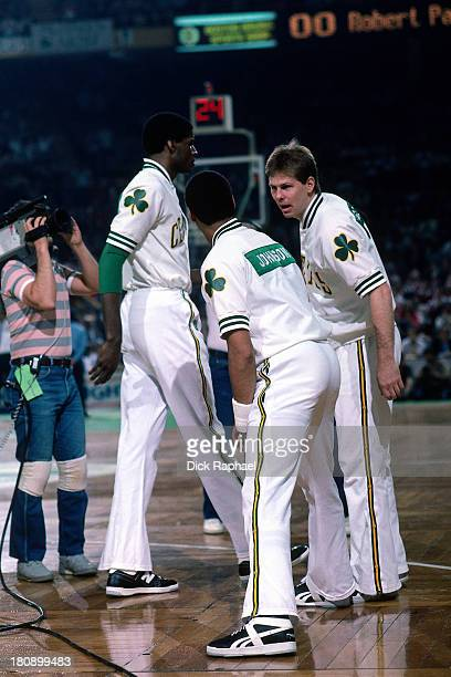Dennis Johnson of the Boston Celtics stretches while talking to teammate Danny Ainge as Robert Parish walks past before a game circa 1986 at the...