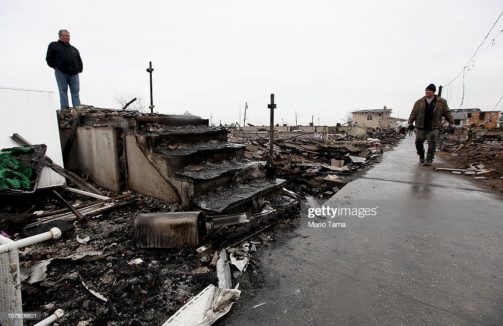 Dennis Kane (L) stands above the charred remains of his destroyed home in the hard hit Breezy Point neighborhood on December 7, 2012 in the Queens borough of New York City. Breezy Point, home to many New York City firefighters and police, lost 111 homes in a fast moving fire during Superstorm Sandy with many more homes severely damaged from flooding.