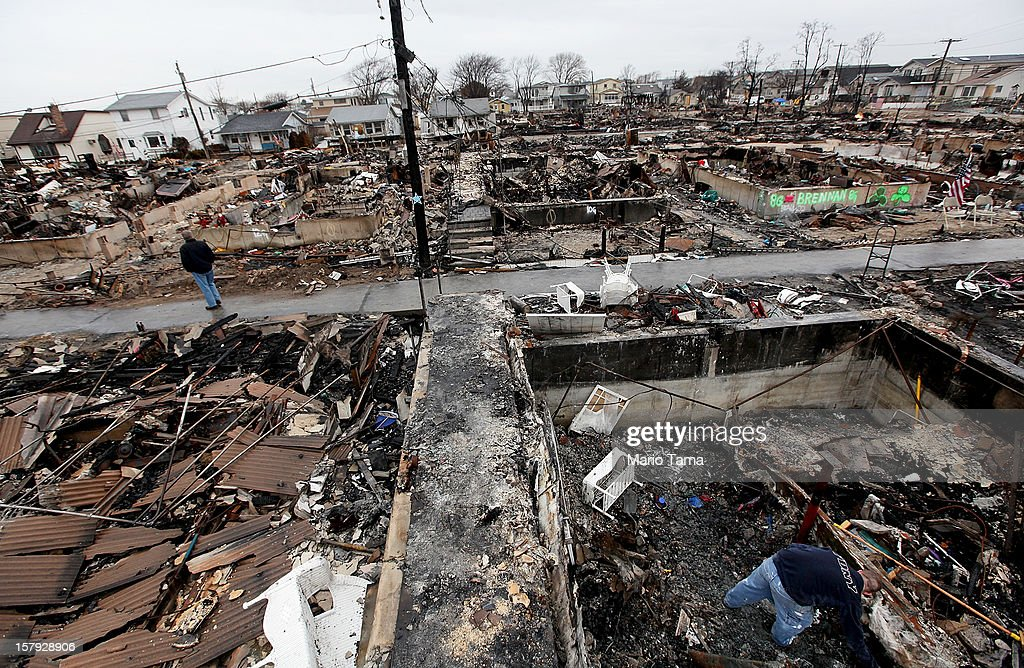 Dennis Kane (L) stands near the charred remains of his destroyed home as his son Chris (R) clears debris in the hard hit Breezy Point neighborhood on December 7, 2012 in the Queens borough of New York City. Breezy Point, home to many New York City firefighters and police, lost 111 homes in a fast moving fire during Superstorm Sandy with many more homes severely damaged from flooding.