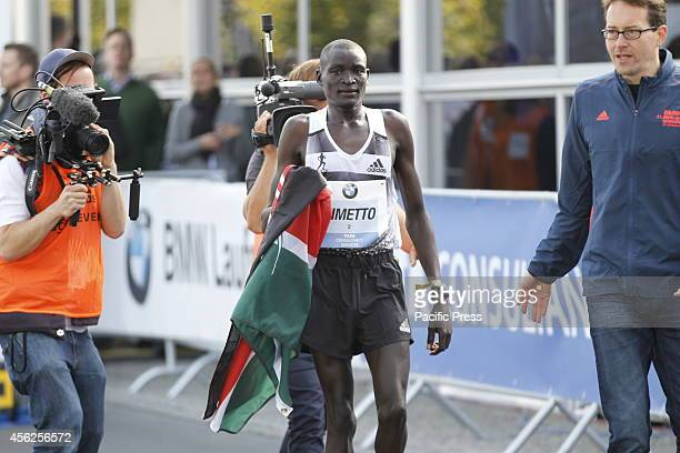 Dennis Kimetto a 30yearold Kenyan wins and proudly holds up his national flag during the 41st BMW Berlin Marathon beating the 20 kilometerrace in two...