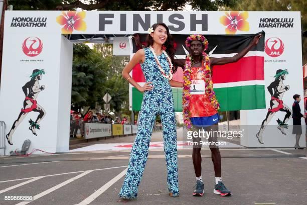 Dennis Kimetto of Kenya poses with Miss Hawaii USA 2018 Julianne Chu after winning the men's marathon during the Honolulu Marathon 2017 on December...