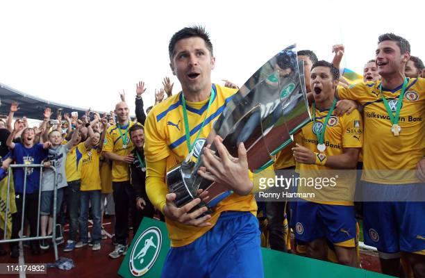 Dennis Kruppke of Braunschweig celebrates promotion to the Second Bundesliga with team mates after the Third League match between Eintracht...