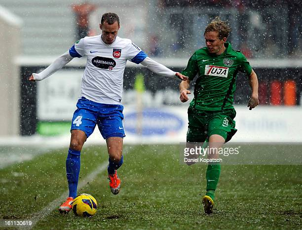 Dennis Malura of Heidenheim is challenged by Dennis Grote of Muenster during the third Bundesliga match between 1 FC Heidenheim and Preussen Muenster...