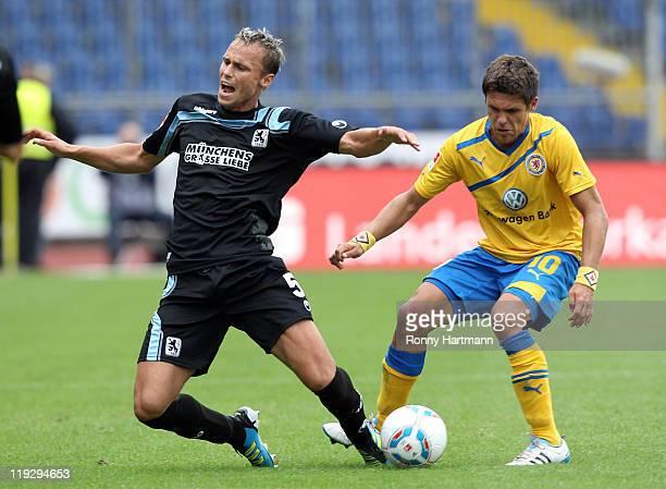 Dennis Malura of Muenchen is challenged by Mirko Boland of Braunschweig during the Second Bundesliga match between Eintracht Braunschweig and TSV...