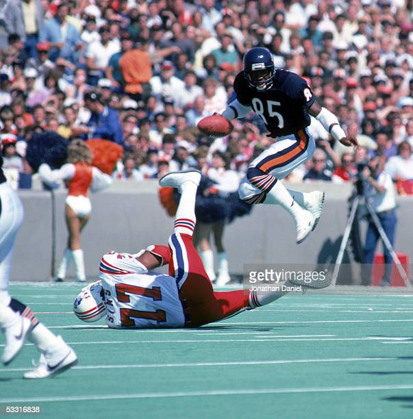 Dennis McKinnon of the Chicago Bears leaps over the tackle attempt of Kenneth Sims of the New England Patriots during the game at Soldier Field on...
