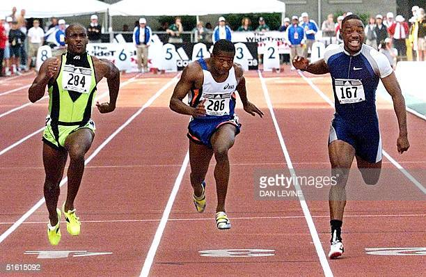 Dennis Mitchell winner of the 100 meter dash Tim Montgomery third place finisher and Tim Harden fourth place cross the finish line of the men's...