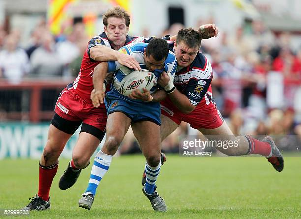 Dennis Moran of Wigan Warriors is tackled by Andy Coley and Mitch Stringer of Salford City Reds during the Engage Super League match between Salford...