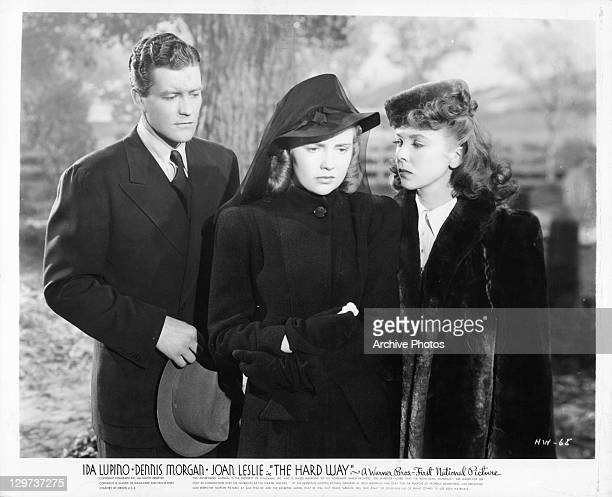 Dennis Morgan standing behind Ida Lupino and Joan Leslie in a scene from the film 'The Hard Way' 1943