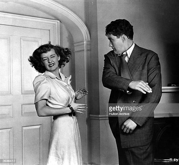 Dennis Morgan the American leading man who was formerly an opera singer violently slaps the face of Bette Davis the American actress in a scene from...