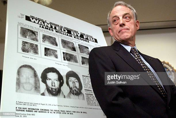 Dennis Nerney the US Attorney's antiterrorism coordinator stands in front of an enlarged FBI wanted poster for Symbionese Liberation Army fugitive...