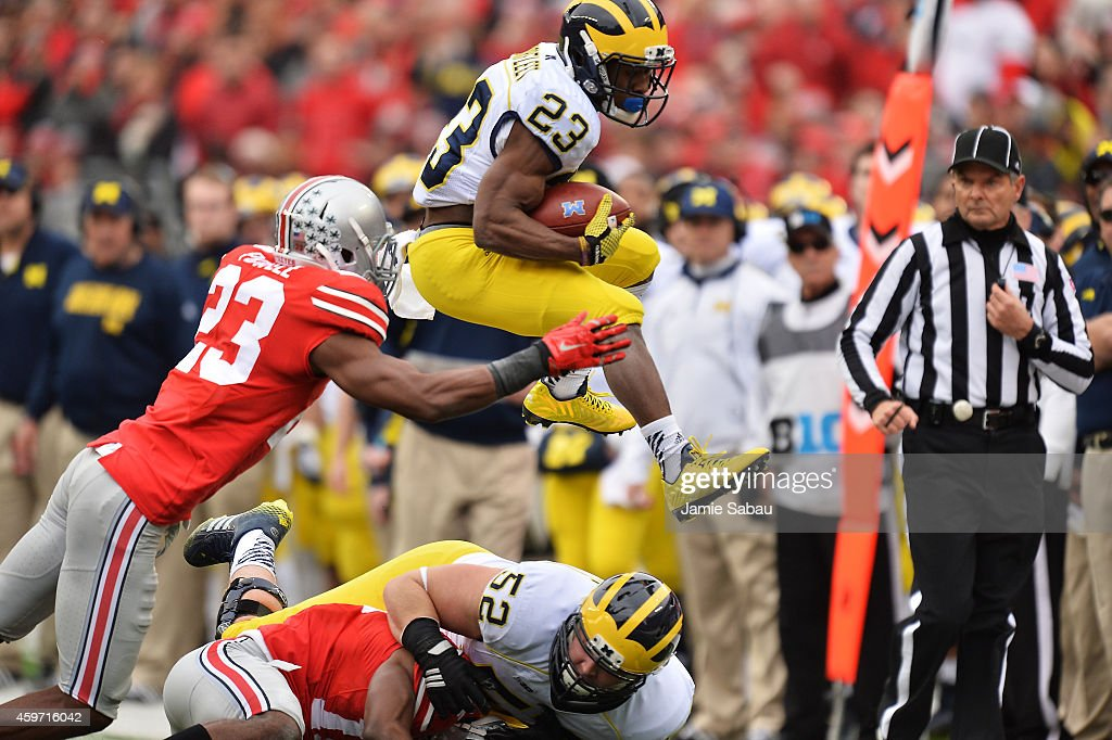 Dennis Norfleet #23 of the Michigan Wolverines leaps over blockers and tacklers to gain a first in the second quarter as he is hit by Tyvis Powell #23 of the Ohio State Buckeyes at Ohio Stadium on November 29, 2014 in Columbus, Ohio.
