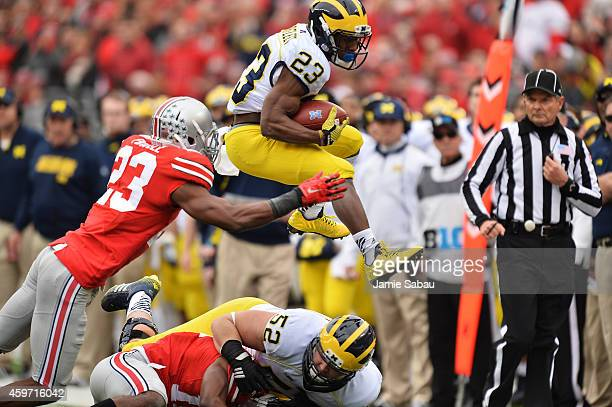 Dennis Norfleet of the Michigan Wolverines leaps over blockers and tacklers to gain a first in the second quarter as he is hit by Tyvis Powell of the...