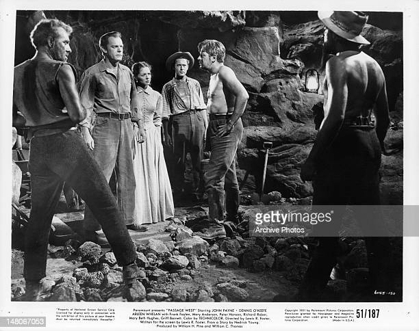 Dennis O'Keefe and Arleen Whelan facing other men in cave in a scene from the film 'Passage West' 1951